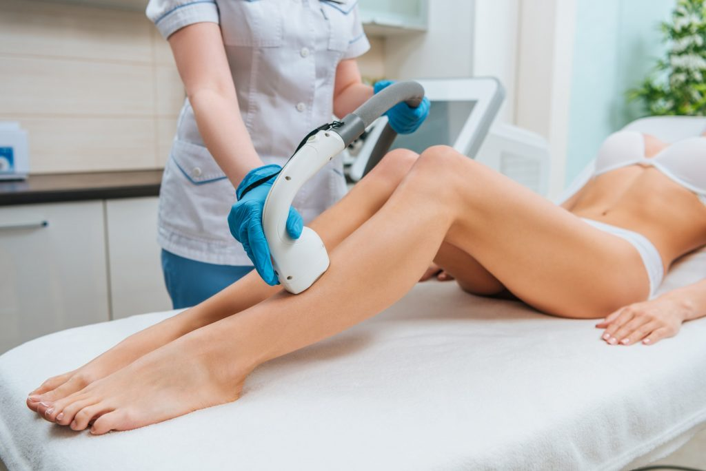 Partial view of cosmetologist in rubber gloves doing laser hair removal procedure on legs